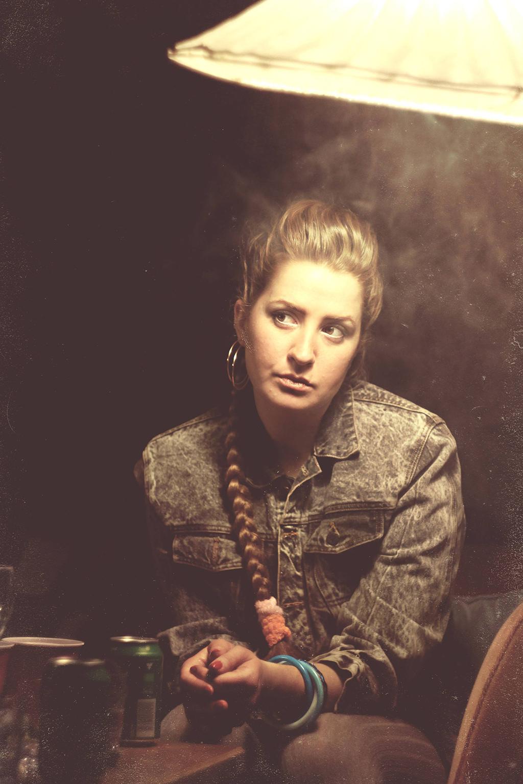 Jessie Lewis Skoglund i mörkt rökigt rum med ölburkar på bordet